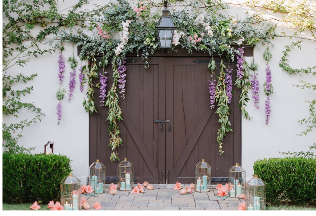 The ceremony took place with the property's carriage house as a backdrop. To complement existing vines on the building, Anne Bowen Dabney of Charleston Stems crafted an arbor-like array of orchid sprays, tulip bundles, and eucalyptus branches, then hung hybrid delphinium and eucalyptus garlands from it. Amaryllis blooms were artfully scattered amid lanterns with celadon green candles. (Image by Natalie Franke Photography)