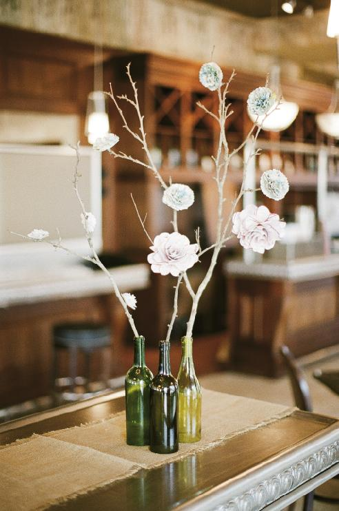 BOTTLED UP: Bottles—with the bases sliced off—became vases. To make paper flowers, search www.WeddingChicks.com for steps.