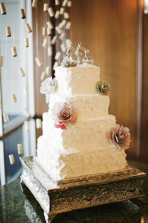 SPECIAL TOUCH: To add cohesiveness to the reception (where florals were comprised of branches sprouting paper flowers the bride crafted from antique maps), Melissa accented the cake from McKenzie's Bake Shop with the same blooms. She added a wire cake topper—a nod to the couple's love of biking—from HeatherBoydWire.com.