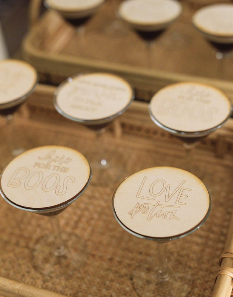 """Passed drinks were topped with wooden coasters engraved with Halloween-themed sayings like """"Here for the Boos,"""" """"Let's give them pumpkin to talk about,"""" and """"Love Potion."""""""