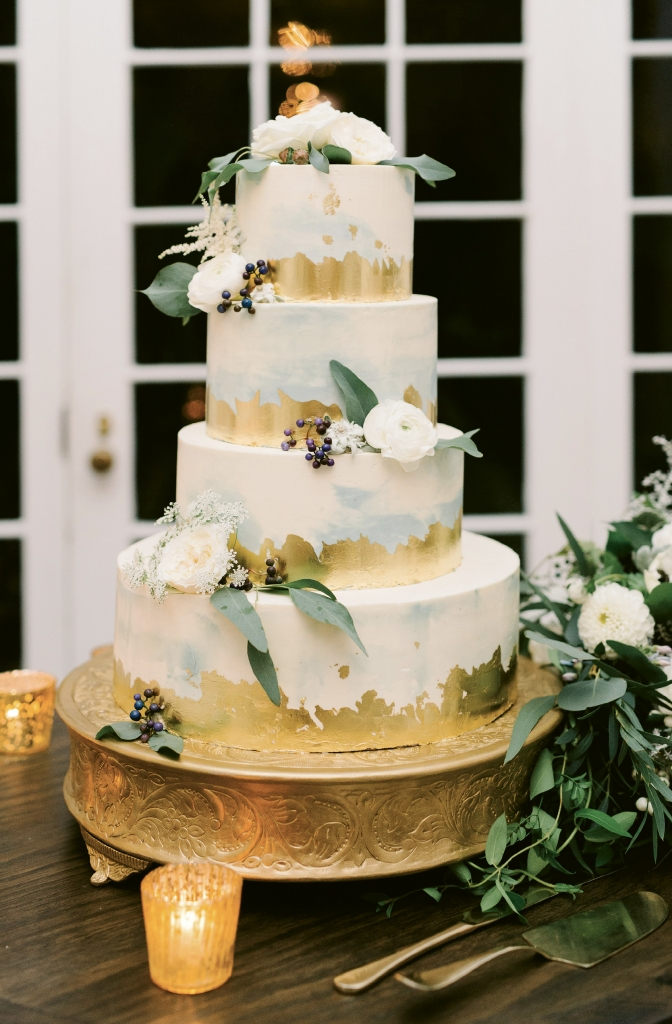 Accented in edible gold leaf, the four-tiered dessert held layers of almond, vanilla, and lemon poppy seed cake iced in buttercream that was painted in a watercolor style.