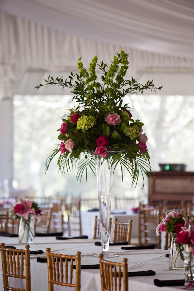 IN BLOOM: Tiger Lily Florist created centerpieces of bright pink roses, lime hydrangea, and green fern. The larger arrangements were elevated, keeping the table conversation-friendly.