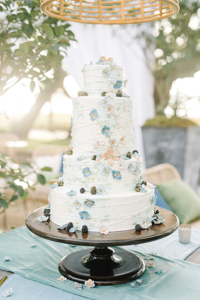 The couple's four-tiered confection by Jim Smeal was comprised of layers of lemon, chocolate raspberry, and caramel cake and adorned with sugar-spun flowers and gold-specked blackberries.