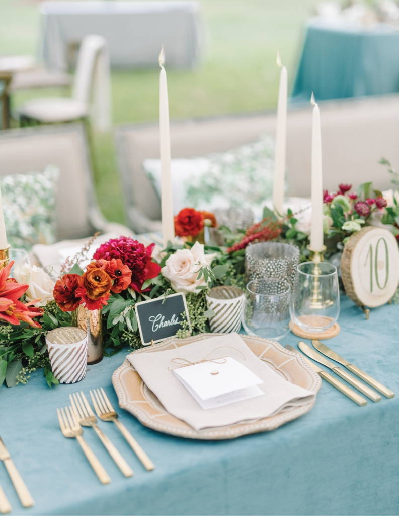 More formal décor elements like gold mercury hurricane candleholders, gleaming cutlery, and stately taper candles are offset by laid-back accents of feathered votives and hand-painted wooden slabs, creating a design that is both rustic and refined.