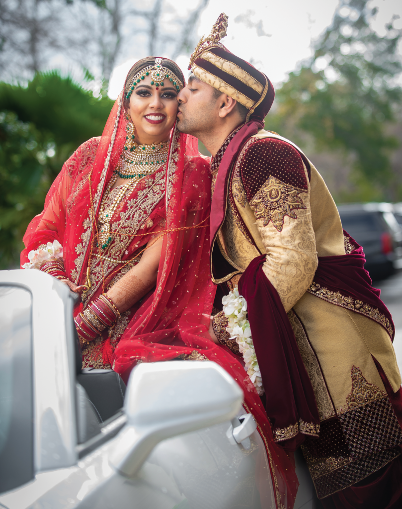 Donning conventional  crimson-colored Indian wedding attire, Swati and Brijesh Patel exchanged vows underneath a cascading floral mandap, or canopy