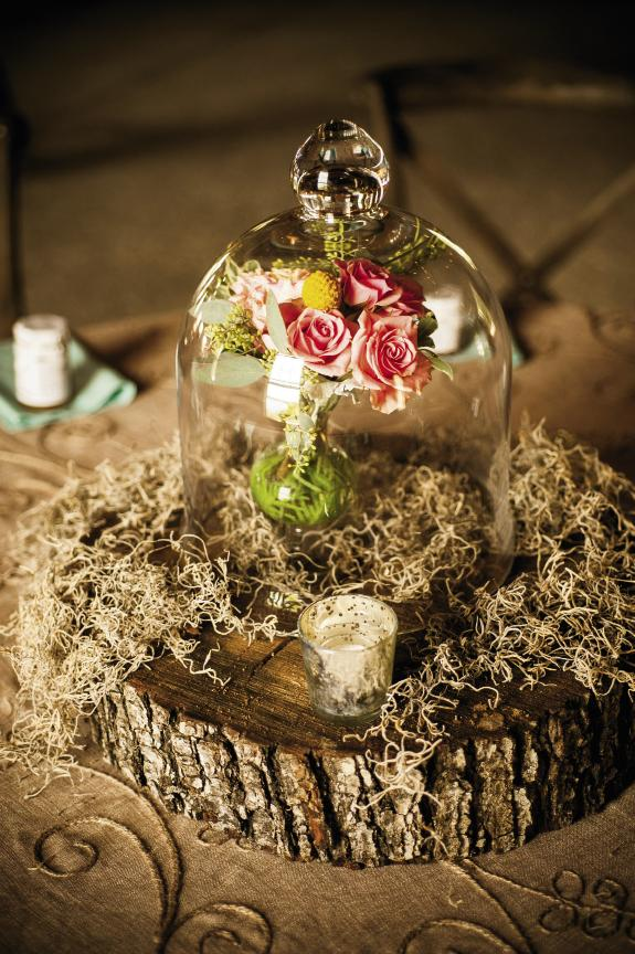 THE BELL JAR: Centerpieces brought the outdoors in with slabs of wood, Spanish moss, and pretty little bouquets magnified by glass cloches.