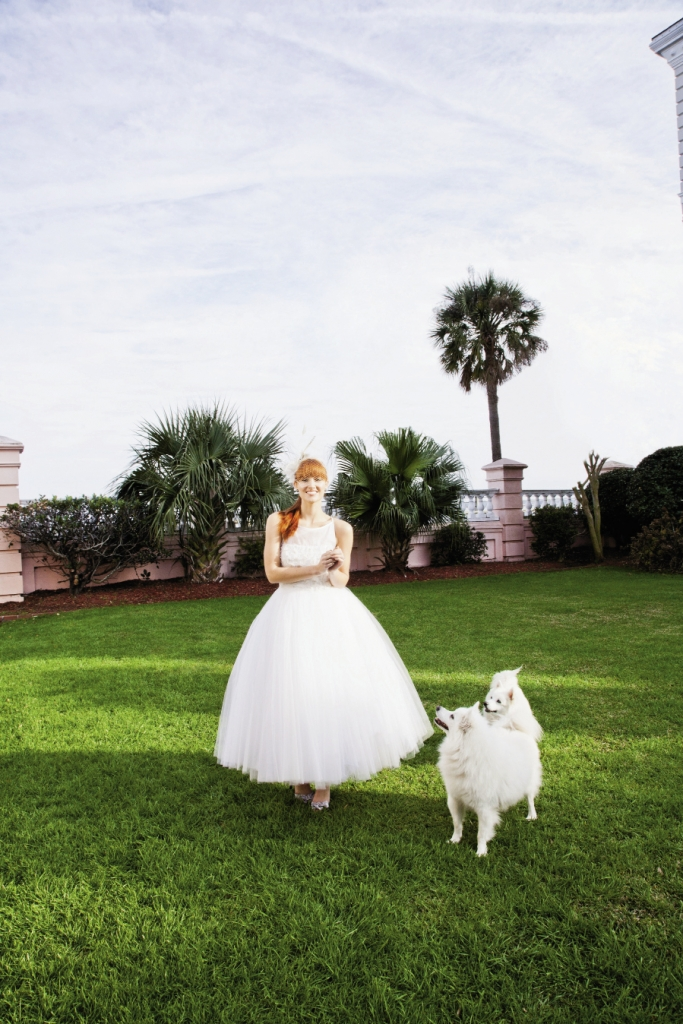 "PUPPY LOVE:  Steven Birnbaum's ""Daisy"" tulle tea-length gown with sheer bateau neckline and floral accents from White. Cage veil headband with feather accents  from Out of Hand. Nina's d'Orsay heels from LulaKate."
