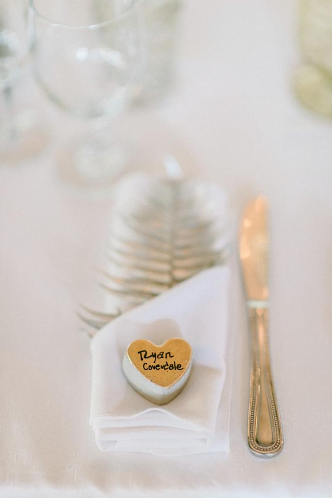 Concrete heart place cards (made with silicone ice cube trays) and gold-painted fern fronds greeted guests. Photograph by Sean Money + Elizabeth Fay.