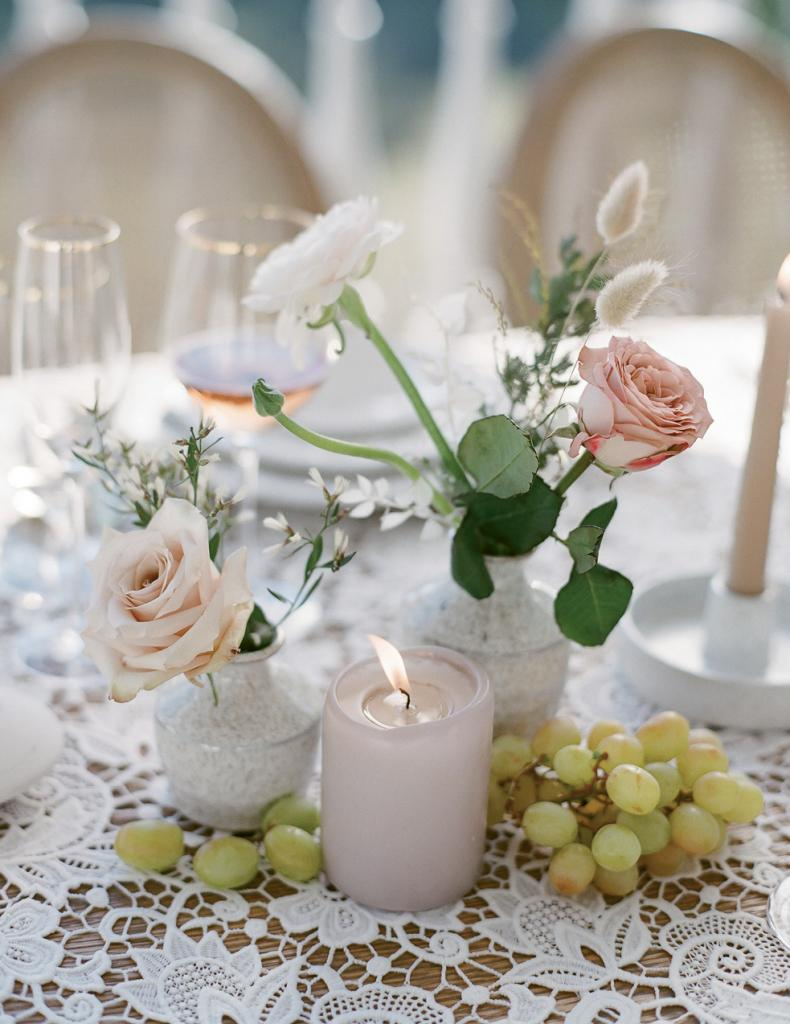 Cluster bud vases filled with select flowers, fresh fruit, and candles for a relaxed tablescape.