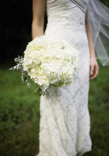 TONE ON TONE: A Charleston Bride took a cue from the bride's Modern Trousseau lace gown to create a textured bouquet of ivory hydrangeas tinged with silver-green Dusty Miller.