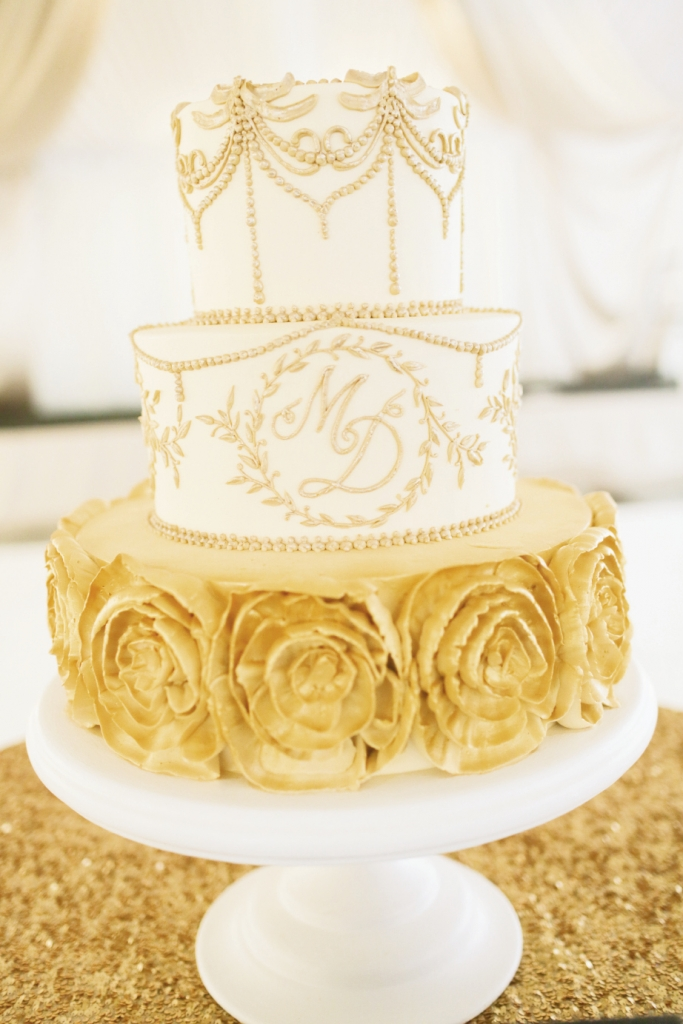 SIMPLY STUNNING:  For Meredith Sever and Dan Tanton's December 2013 fête, Wedding Cakes by Jim Smeal fused patterns from the stationery suite and the bride's gown with gold—the reception's star hue—for a  brilliant confection.