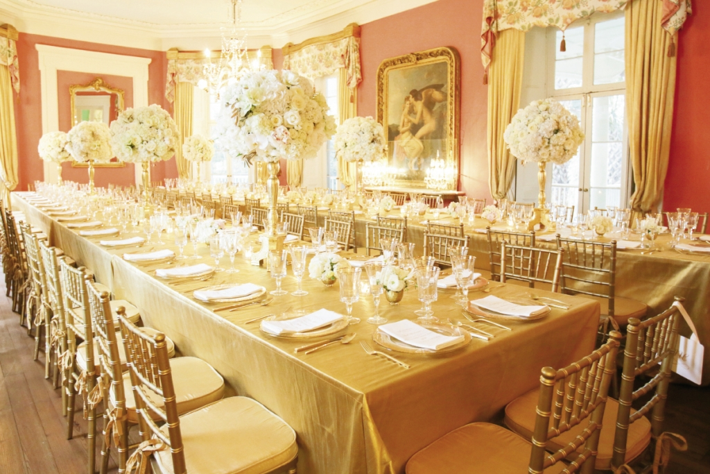 """When you are working with a strong color like gold,"" says bride (and planner) Meredith, ""do a mock-up in the space with a set of the tablescape elements, linens, and chairs to see how the whole picture works together."" Here, golden tablecloths and chiavari chairs are a natural extension of the room's gilded frames. Image by The Connellys."