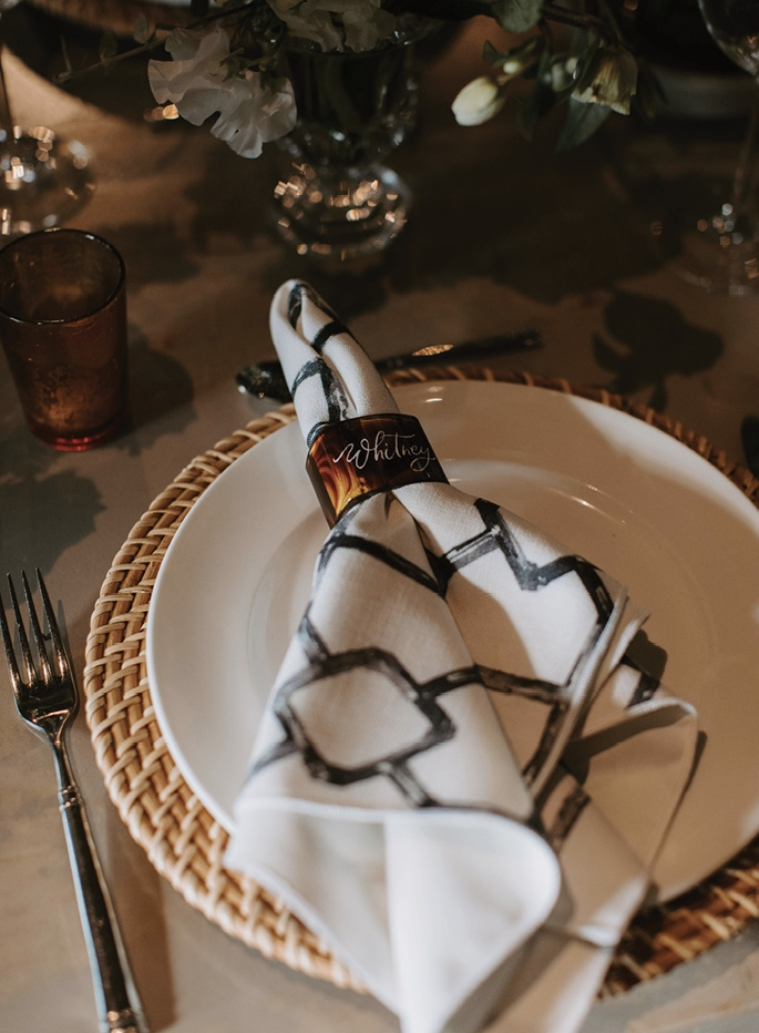 The décor featured rattan, checkered marble, greenery, stoneware, pewter, candles, and personalized tortoiseshell napkin rings.