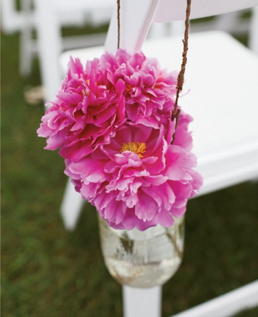 POSY PALS: Raspberry-hued peonies tucked into Mason jars dressed the aisle.