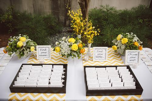 "SIT A SPELL: Guests found their seat numbers thanks to a playful escort card design. Jacqueline explains the method behind her display: ""Instead of organizing all of the cards on ribbon or in trays, we did both, mixing them with candles and floral arrangements."""
