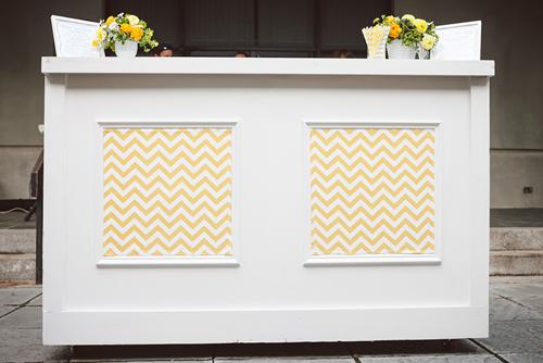 SPICE THINGS UP: Jacqueline also used spare yellow chevron fabric to panel the reception bar, transforming it from a standard white to a colorful custom piece.