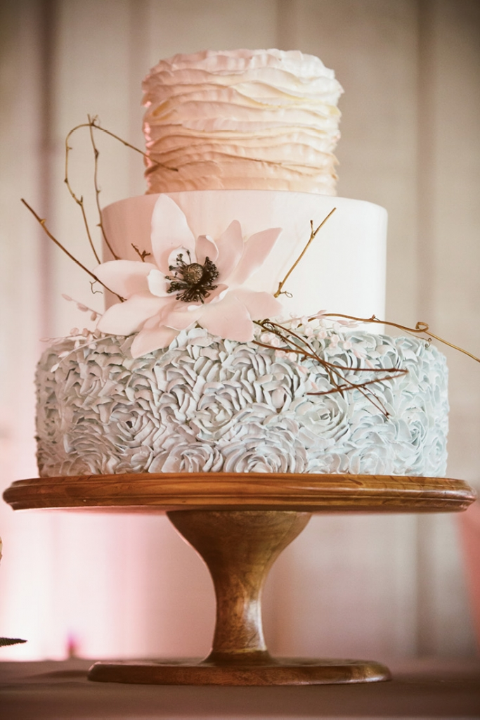 "The Wedding Cakes by Jim Smeal creation was a true collaboration. Catherine chose the ruffles while Christina suggested the magnolia-inspired accent floral. ""It needed some kind of natural, rustic element to make it a little less formal and a lot more fun,"" says Christina, ""so we added the twigs and voilà!""  <i>Amelia + Dan Photography</i>"
