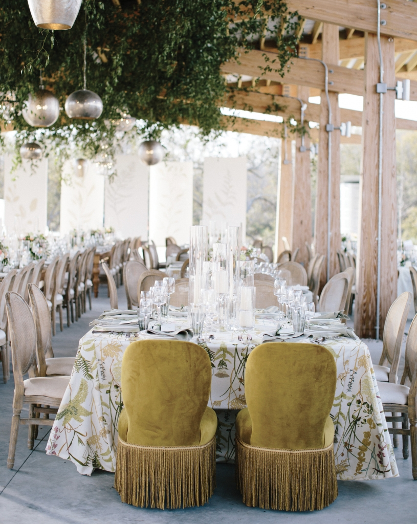 A botanical look was influenced by The Bend's conservation-driven mission, and was played up in the hand-painted seating chart and stage backdrop and in the custom table linens, napkins, and butler service towels, which were sourced and produced by Ooh! Events.