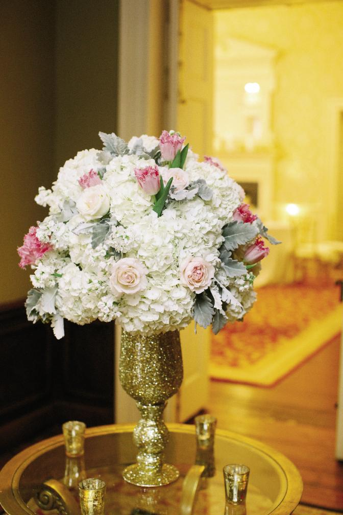 Think big (and gold) for entrance décor. Here, glitter completely covers a chalice topped with an arrangement of hydrangeas, fringe tulips, garden roses, hypericum berries, ranunculus, and sweet peas in cream, blush, and caramel colors by Whitney Randall of Branch Design Studio.