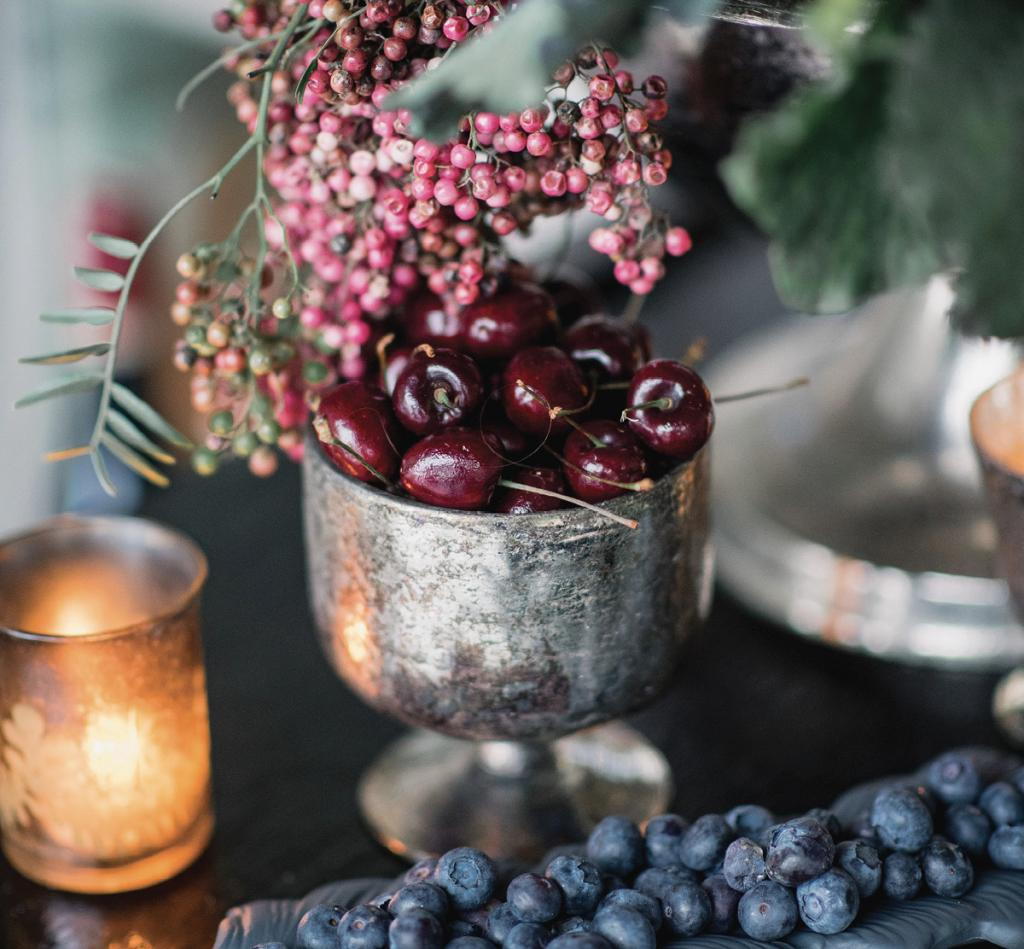 Clusters of rich-hued fruit—cherries, blueberries, blackberries, and pomegranates—offered organic opulence to reception tablescapes.