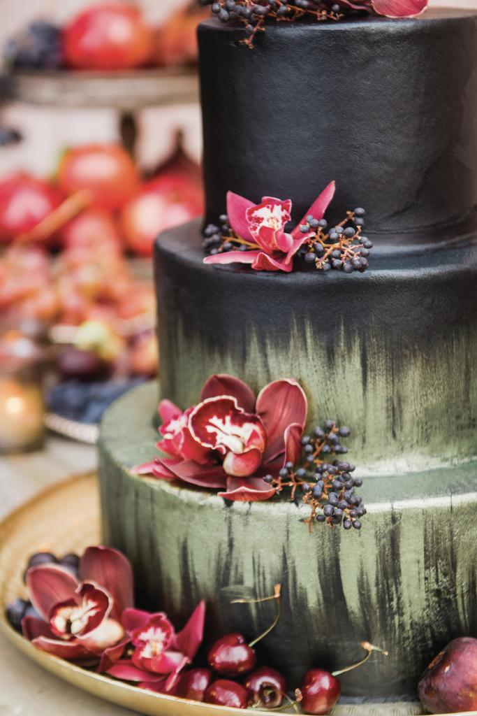 The red velvet cake was hand-painted and topped with fresh fruit and orchids, while tables were covered in lush florals and dripping candles.