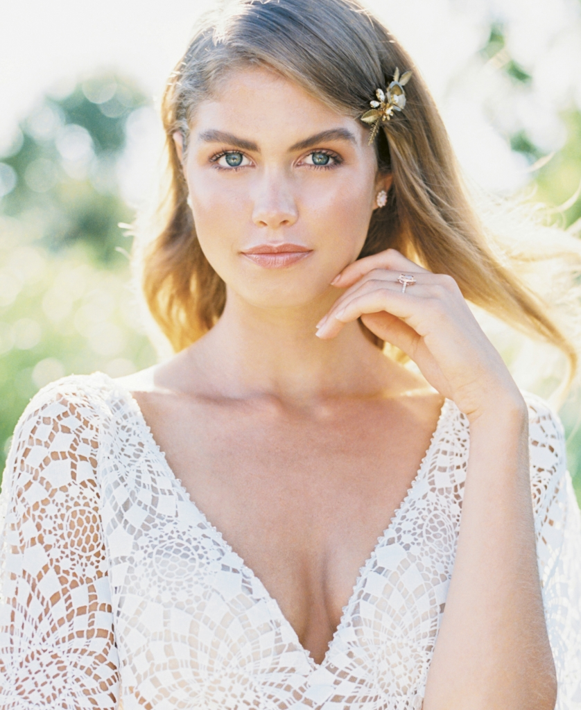 "Casablanca's ""Cheyenne"" laser-cut lace and stretch satin georgette gown from Palmetto Bridal Boutique. Gold hairpin by Emma Katzka.  Opal and diamond earrings and morganite and diamond rose gold ring, both from Gold Creations. Location: Seabrook Island Club Equestrian Center. Photograph by Perry Vaile"
