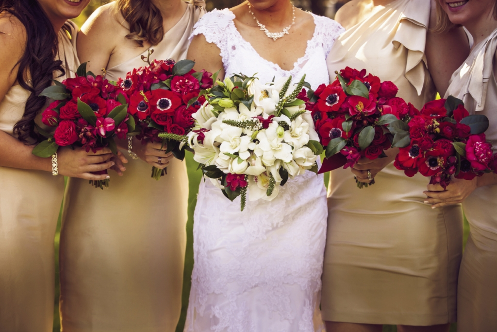 RICH HUES: Tiger Lily crafted the crimson ceremony florals for the bridesmaids, while the bridal bouquet was awash in white.