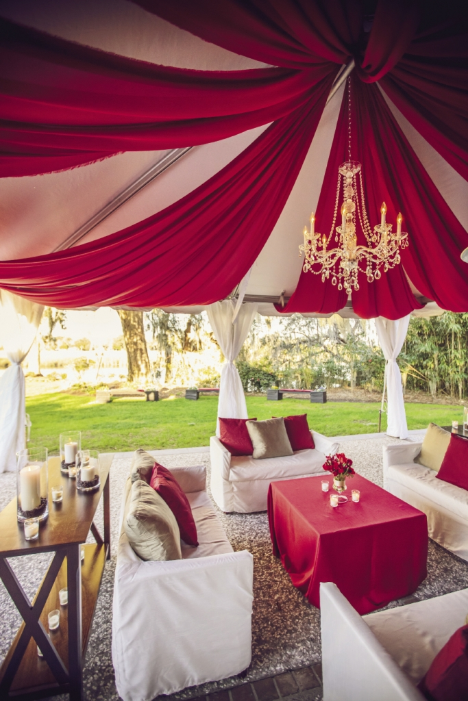 COLORFUL CANOPY: Cindy Zingerella of Engaging Events used swaths of red fabric and a crystal chandelier to give the lounge an upscale, finished look.