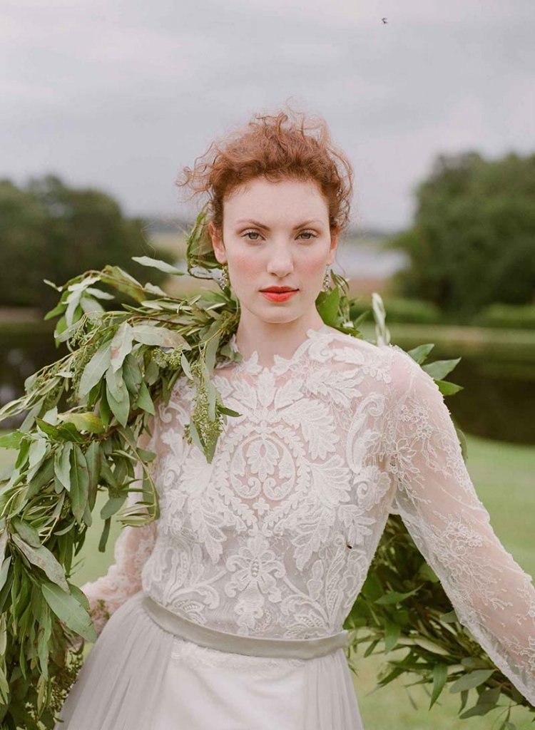 "Emily Kotarski's ""Buckingham"" silk gown with illusion lace top, faille skirt, and detachable chiffon train from Emily Kotarski Bridal. Sapphire and diamond earrings from Croghan's Jewel Box. Seeded eucalyptus garland from Out of the Garden.  <i>Photograph by Corbin Gurkin</i>"