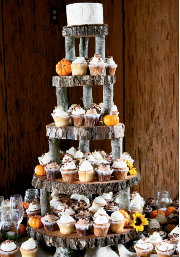 TALL NUMBER: To tie the dessert table to the rest of the wedding, they used a rough-hewn, tiered wooden stand, which Rheney decorated with yellow blooms and tiny orange pumpkins to reiterate the wedding's palette.