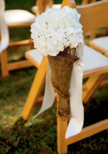 Aisle markers of simple white hydrangea wrapped in burlap complemented the scenery.