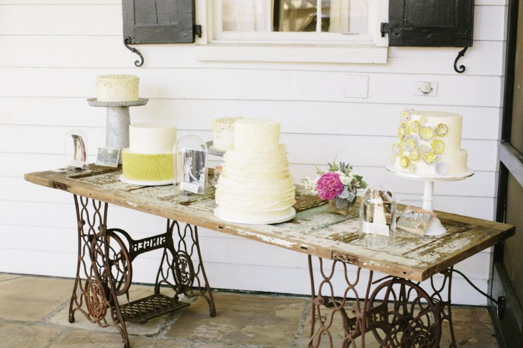 COME ORIGINAL: Forget the folding table—Sarah arranged wedding cakes upon an old farmhouse door supported by twin cast-iron Singer sewing machine bases.