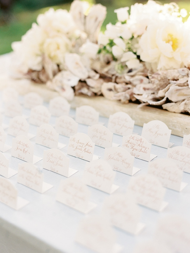 Classic escort cards stood at attention before clusters of shells mixed with fluffy blooms.