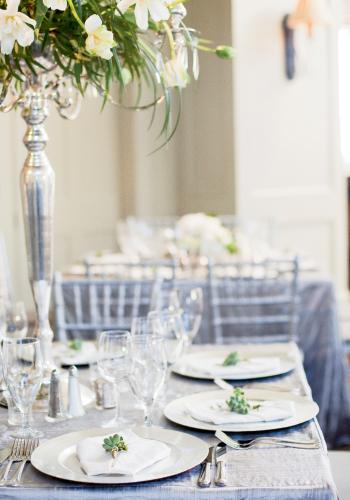 SILVER SETTING: Custom-made silver linens, silver candelabras, silver chargers, and a sea of icy crystal were offset by white French tulips, green bear grass, and posies of Dusty Miller winter berries at each place setting.