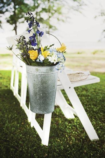 JUST PICKED: In keeping with the wedding's casual feel, blue thistle, delphinium, freesia, and hydrangea were loosely dropped into metal buckets.
