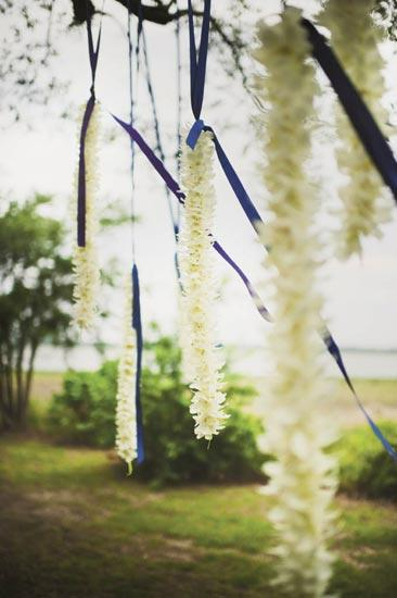 HANGING OUT: Wedding designer Stacey Fraunfelter of Red Letter Events hung garlands of white dendrobium from blue ribbons looped around three branches.