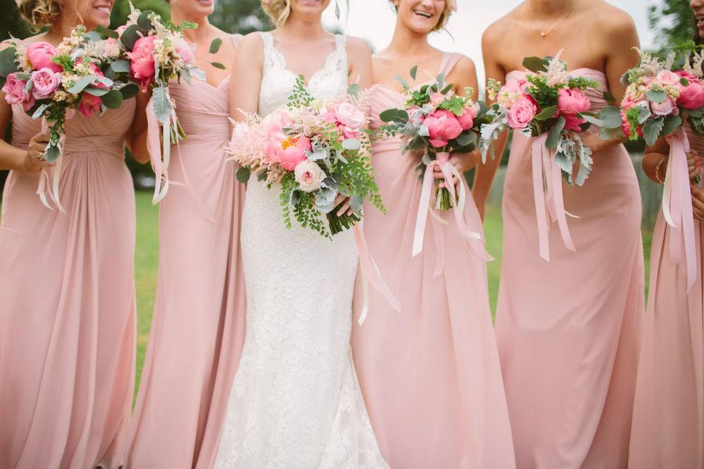 Bride's gown by Marisa Bridals. Bridesmaid dresses by Watters, available locally through Bella Bridesmaids. Bouquets by Branch Design Studio. Photograph by Juliet Elizabeth.