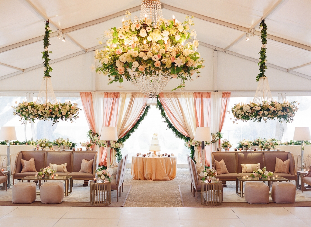 "Showstopping floral chandeliers drew eyes upward while a mix of traditional and modern furnishings filled the tent below. ""Meggie is super hip and wanted a youthful vibe, so we layered in clean touches, like Lucite-and-gold barstools,"" says Calder. <i>Image by Lucy Cuneo Photography</i>"