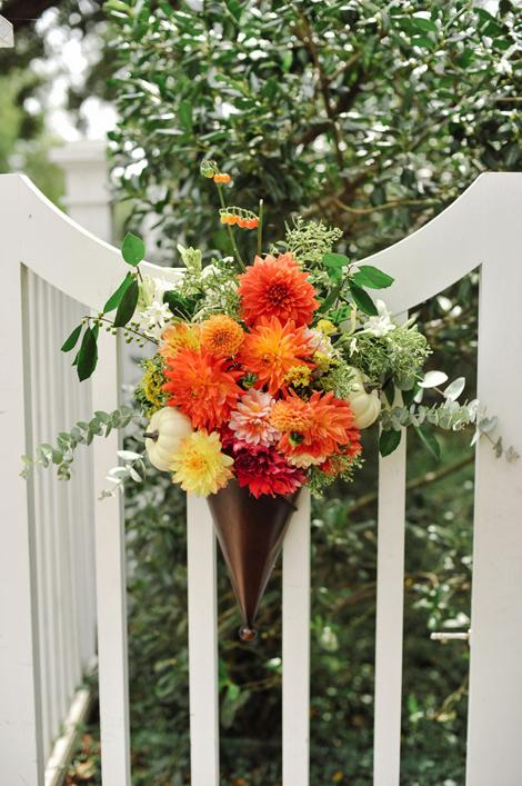 HUNG WITH CARE: Adorning the Governor Thomas Bennett House's fence were inverted copper cones bursting with orange and yellow dahlias and mums, eucalyptus leaves, and mini pumpkins.