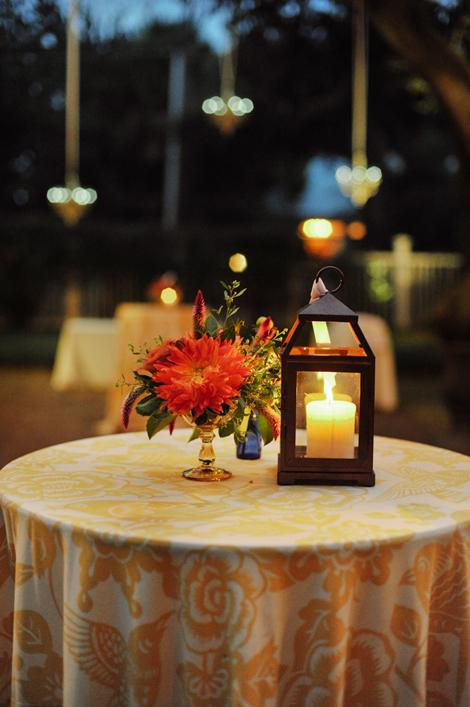 FIERY NIGHT: As the sun set, candlelight brightened the reception tables while dangling outdoor chandeliers and café lights filled the garden with a romantic glow.
