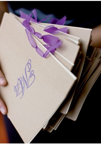 TO THE LETTER: Butcher paper-colored programs emblazoned with violet monograms echoed the location's palette and one of the wedding's sassy shades.